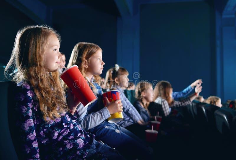 Glimlachende jonge toeschouwers die popcorn eten en op beeldverhaal in bioskoop letten stock foto