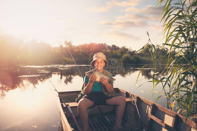 Glimlachende jonge vissersjongen die zijn eerste vissenvangst tonen stock afbeeldingen