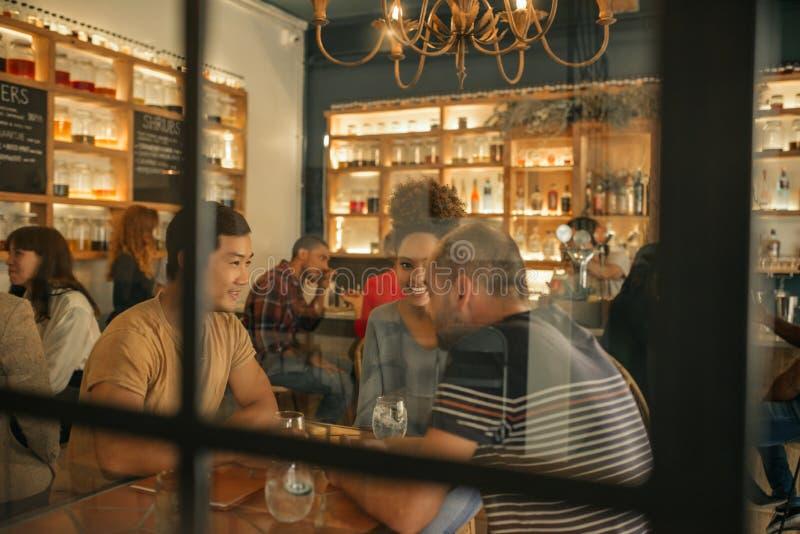 Glimlachende jonge vrienden die samen in een bar zitten die dranken hebben stock afbeeldingen