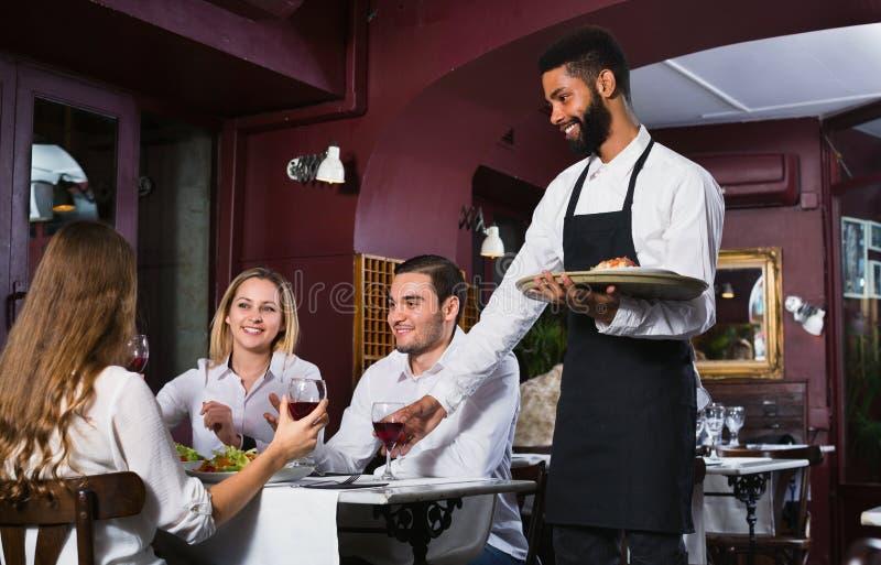 Glimlachende jonge vrolijke kelner die volwassenen behandelen stock afbeelding