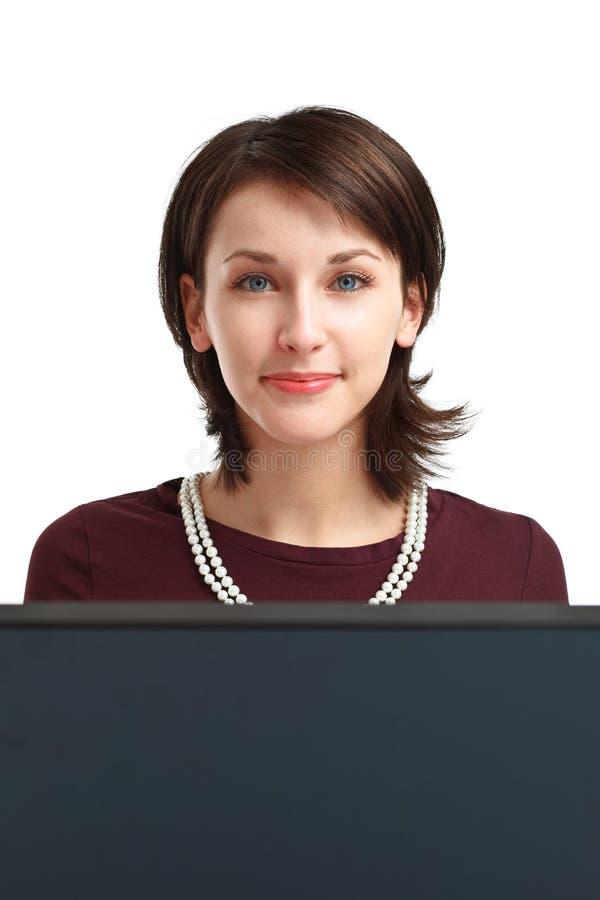 Glimlachende jonge vrouw achter de computer royalty-vrije stock afbeeldingen