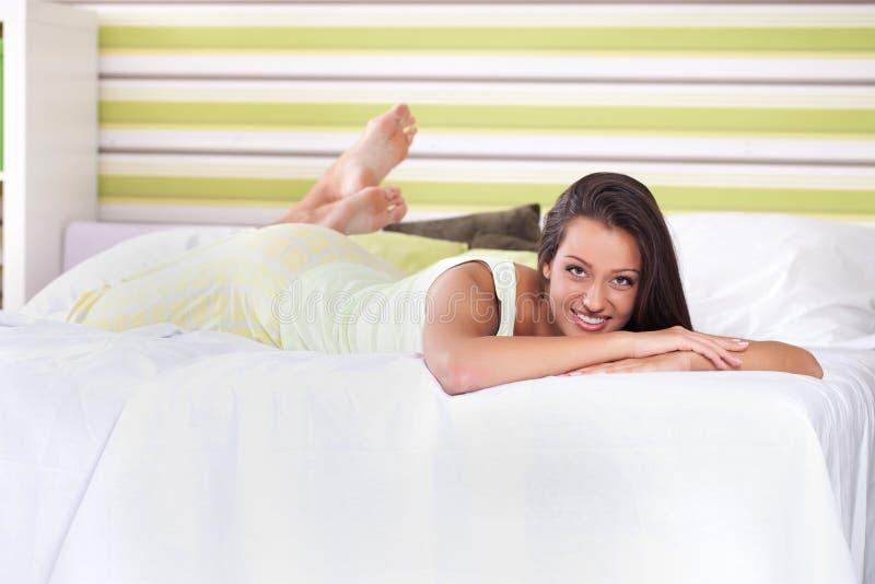 Glimlachende jonge vrouw in bed royalty-vrije stock fotografie