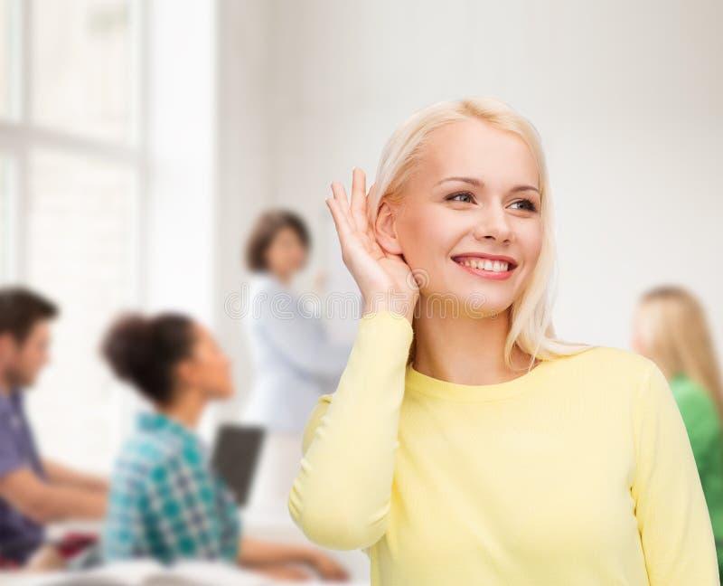 Glimlachende jonge vrouw die aan roddel luisteren stock afbeeldingen