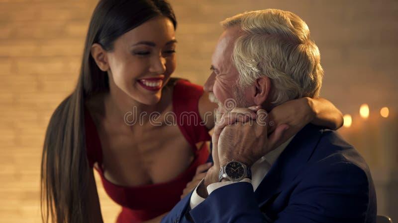 Glimlachende jonge vrouw die bejaarde heer, romantische datum, onbeantwoorde liefde koesteren stock afbeeldingen