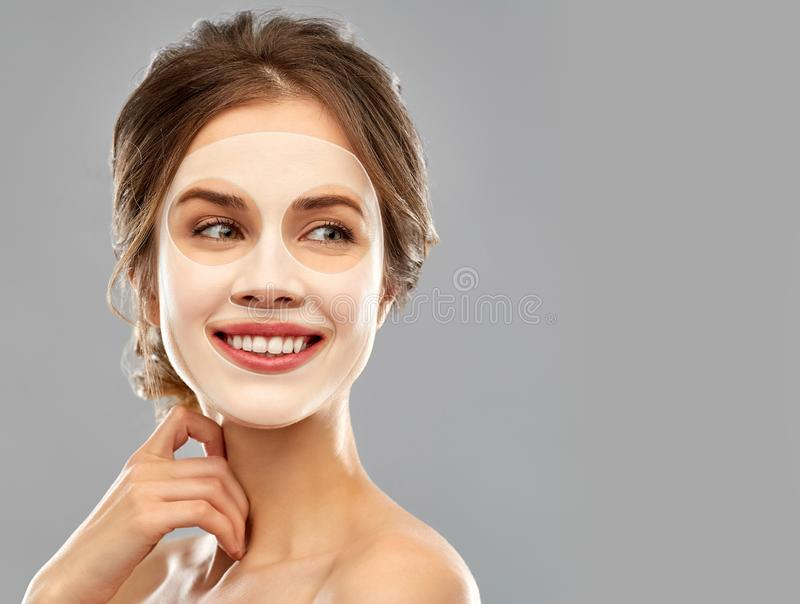 Glimlachende jonge vrouw die blad gezichtsmasker dragen stock afbeeldingen