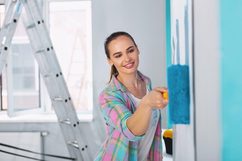 Glimlachende jonge vrouw die de muren schilderen royalty-vrije stock afbeelding