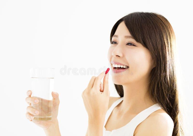 Glimlachende jonge vrouw die de pil eten royalty-vrije stock afbeeldingen