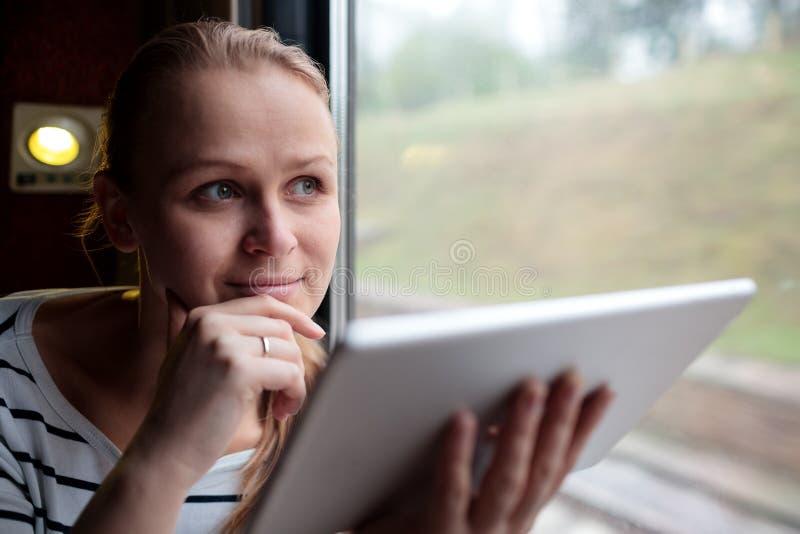 Glimlachende jonge vrouw die door trein reizen stock foto's