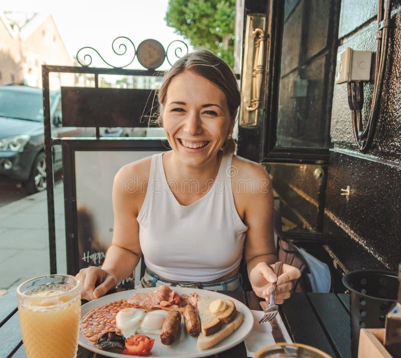 Glimlachende jonge vrouw die een Engels ontbijt eten stock fotografie