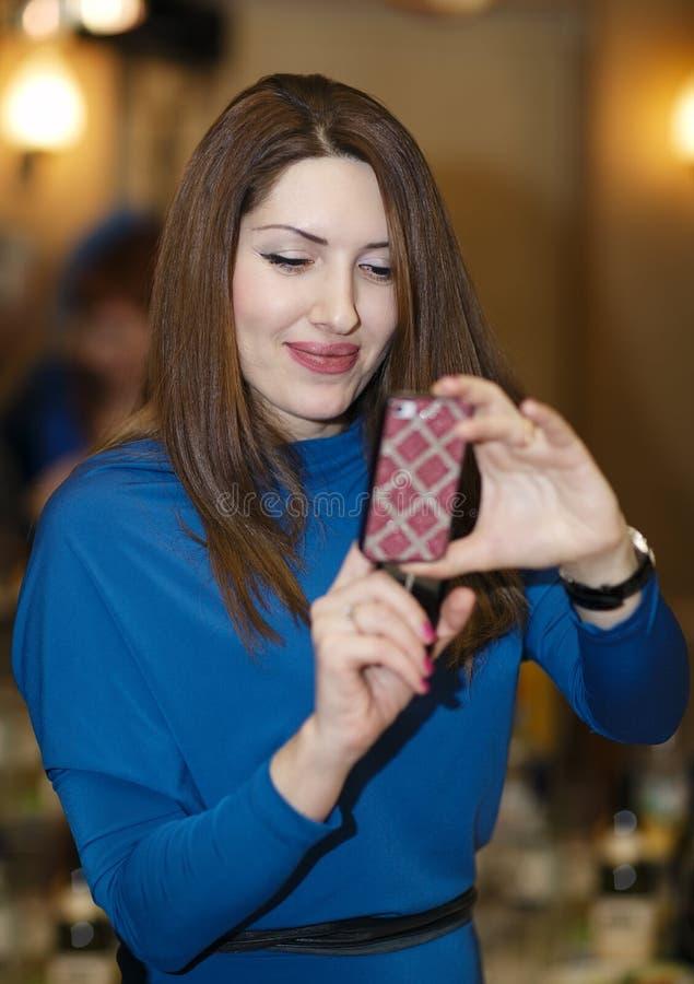 Glimlachende jonge vrouw die een smartphone gebruiken stock afbeelding