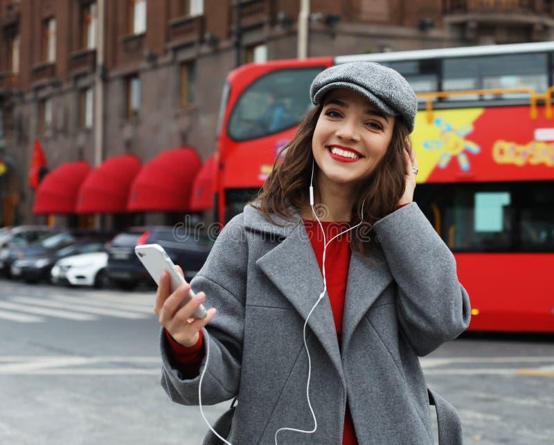 Glimlachende jonge vrouw die en op smartphone in de de herfststad roepen spreken royalty-vrije stock afbeelding