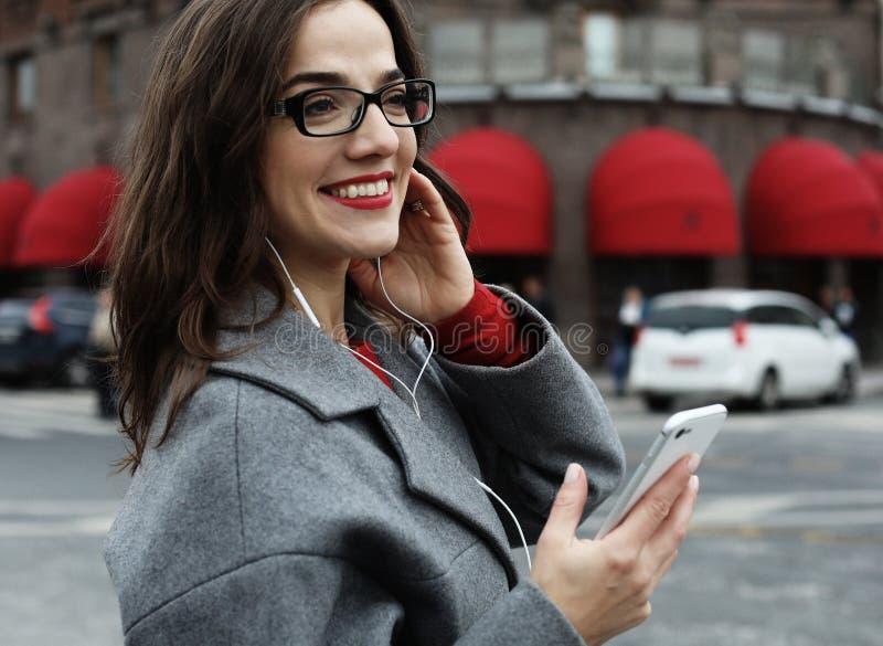 Glimlachende jonge vrouw die en op smartphone in de de herfststad roepen spreken royalty-vrije stock fotografie