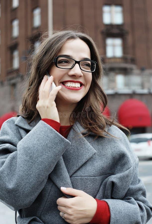 Glimlachende jonge vrouw die en op smartphone in de de herfststad roepen spreken stock fotografie