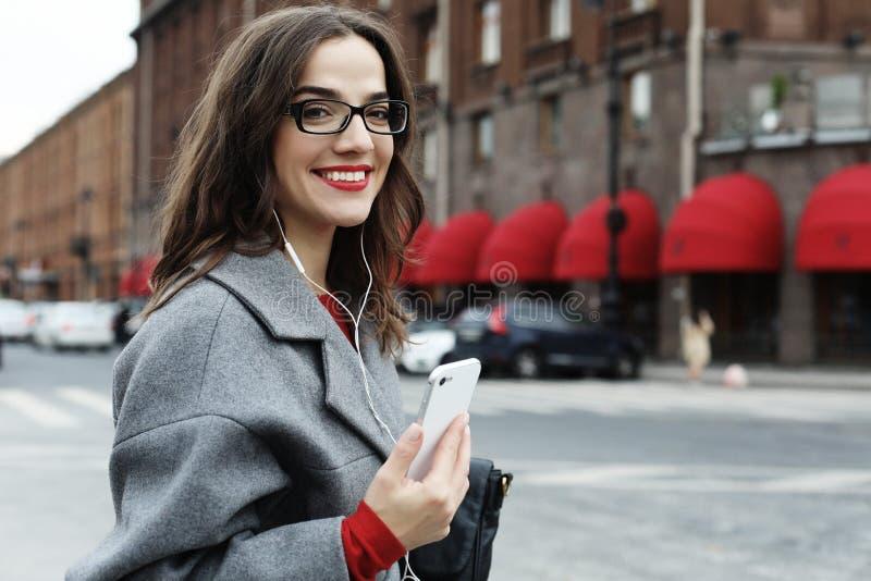 Glimlachende jonge vrouw die en op smartphone in de de herfststad roepen spreken stock afbeelding