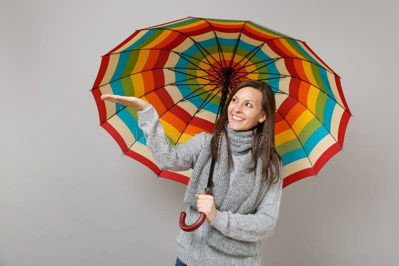 Glimlachende jonge vrouw die in grijze sweater, sjaal hand richten die kleurrijke die paraplu houden op grijze muurachtergrond wo royalty-vrije stock fotografie