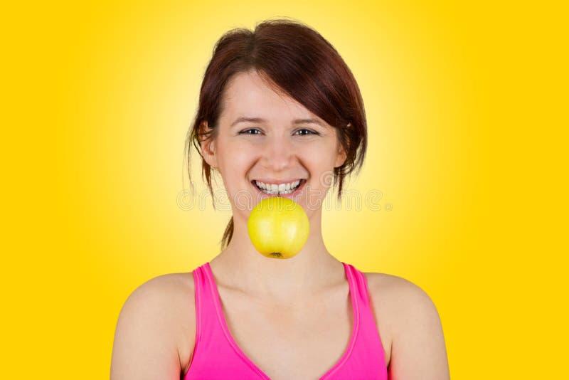 Glimlachende jonge vrouw die groene appel in haar tanden houden royalty-vrije stock afbeeldingen