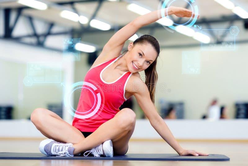 Glimlachende jonge vrouw die in gymnastiek uitoefent stock afbeelding