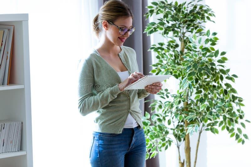 Glimlachende jonge vrouw die haar digitale tablet thuis gebruiken stock foto's
