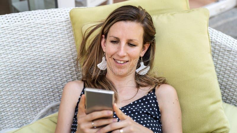 Glimlachende jonge vrouw die haar mobiele telefoon doorbladeren royalty-vrije stock fotografie