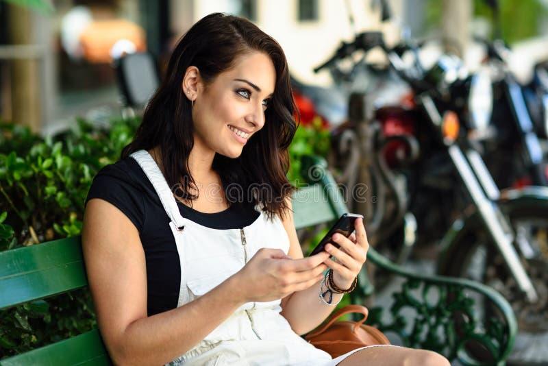 Glimlachende jonge vrouw die haar slimme telefoon in openlucht met behulp van royalty-vrije stock afbeelding