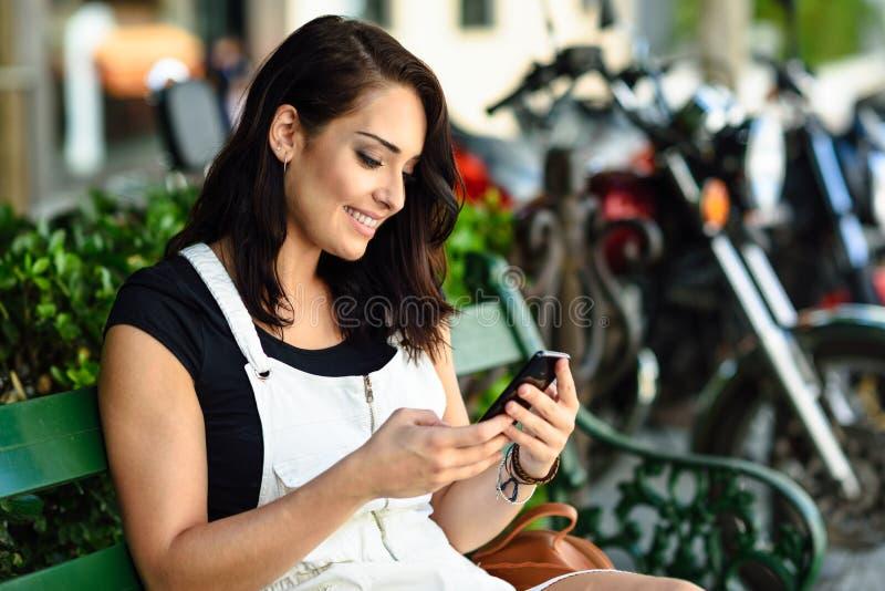 Glimlachende jonge vrouw die haar slimme telefoon in openlucht met behulp van stock fotografie