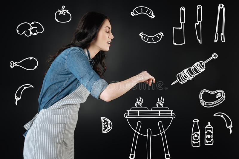 Glimlachende jonge vrouw die kruiden toevoegen terwijl het maken van barbecue royalty-vrije stock afbeeldingen