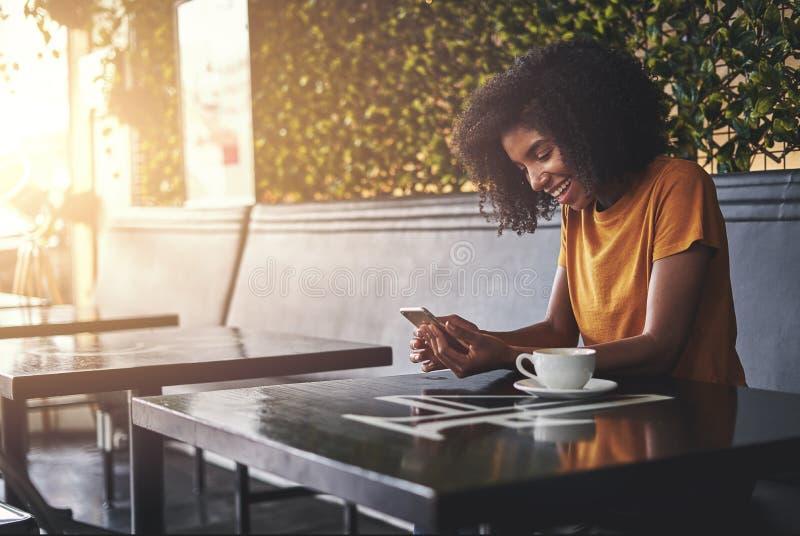 Glimlachende jonge vrouw die mobiele telefoon in koffie met behulp van royalty-vrije stock fotografie