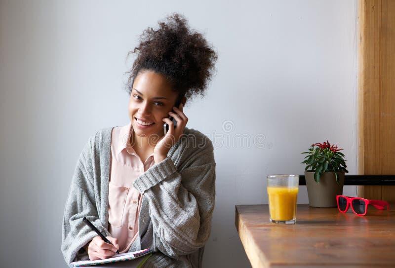 Glimlachende jonge vrouw die nota's met pen en document thuis nemen stock foto