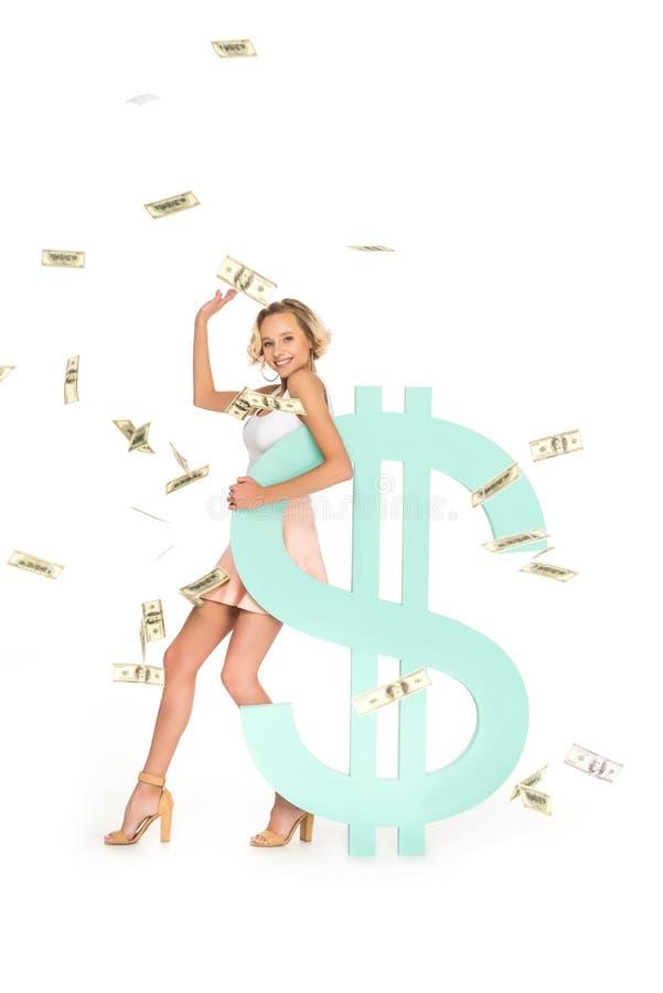 glimlachende jonge vrouw die op dollarteken leunen met dalende rond dollars stock afbeeldingen