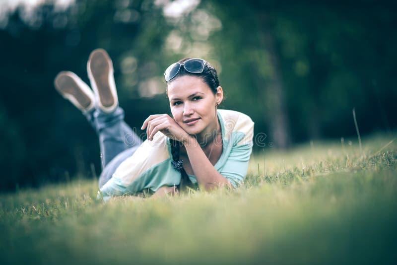 Glimlachende jonge vrouw die op gras in de zomerdag liggen royalty-vrije stock foto's