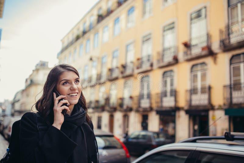 Glimlachende jonge vrouw die op haar smartphone op de straat spreken Communicerend met vrienden, vrije vraag en berichten voor jo royalty-vrije stock fotografie