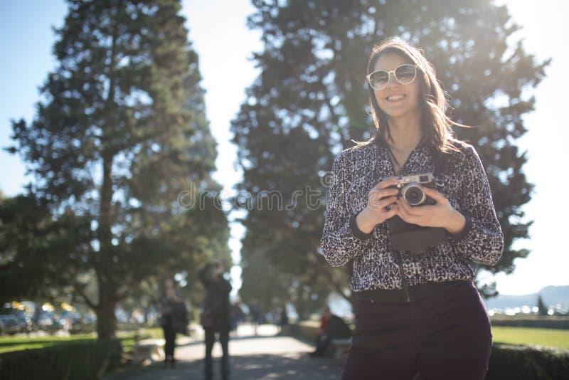 Glimlachende jonge vrouw die op haar smartphone op de straat spreken Communicerend met vrienden, vrije vraag en berichten voor jo stock foto