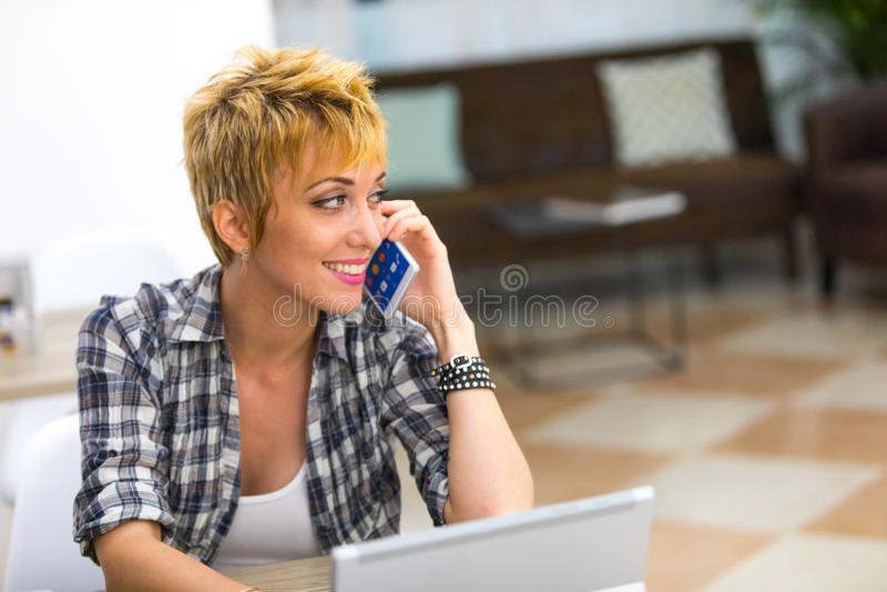 Glimlachende jonge vrouw die op mobiel haar spreken royalty-vrije stock foto's
