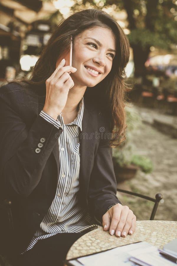Glimlachende jonge vrouw die op telefoon, het uitwerken spreken van bureau stock foto's