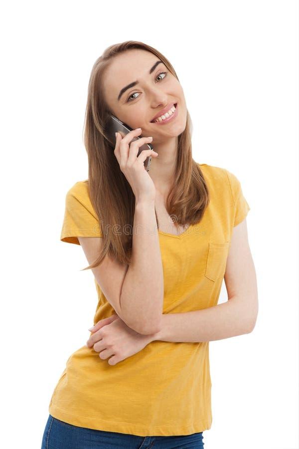 Glimlachende jonge vrouw die die op telefoon spreken op wit wordt geïsoleerd Exemplaarruimte en manier Spot omhoog Gele t-shirt stock fotografie
