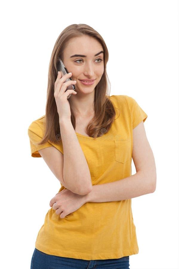 Glimlachende jonge vrouw die die op telefoon spreken op wit wordt geïsoleerd Exemplaarruimte en manier Spot omhoog Gele t-shirt royalty-vrije stock fotografie