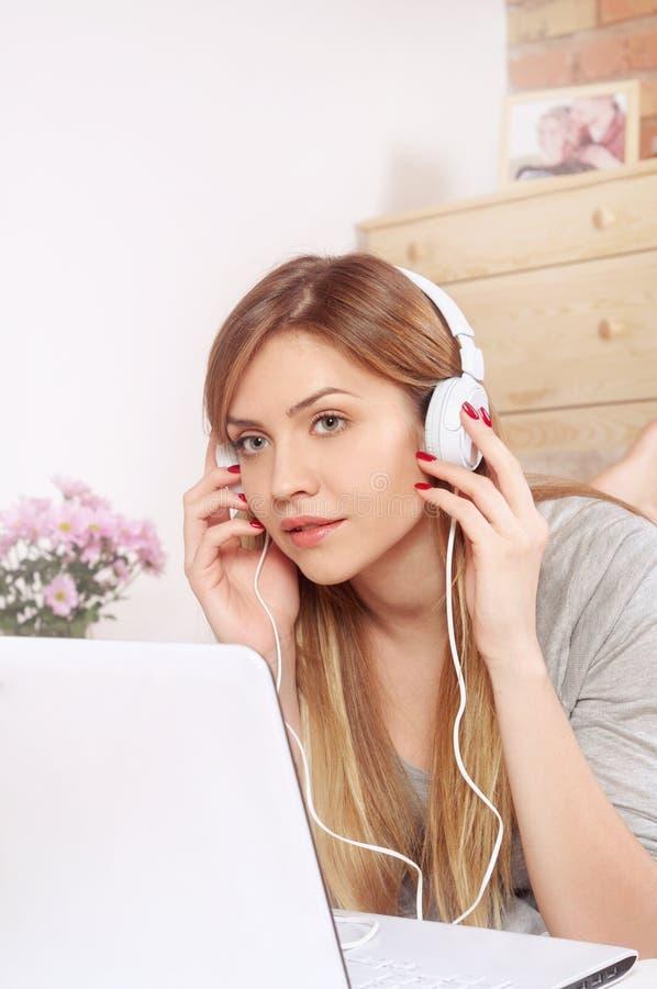 Glimlachende jonge vrouw die op uw laptop en het luisteren muziek thuis kijken royalty-vrije stock afbeeldingen