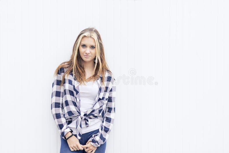 Glimlachende jonge vrouw die op witte achtergrond camera bekijken royalty-vrije stock afbeeldingen