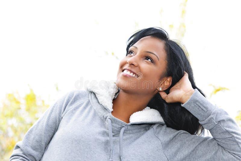 Glimlachende jonge vrouw die in openlucht omhoog kijkt stock afbeeldingen