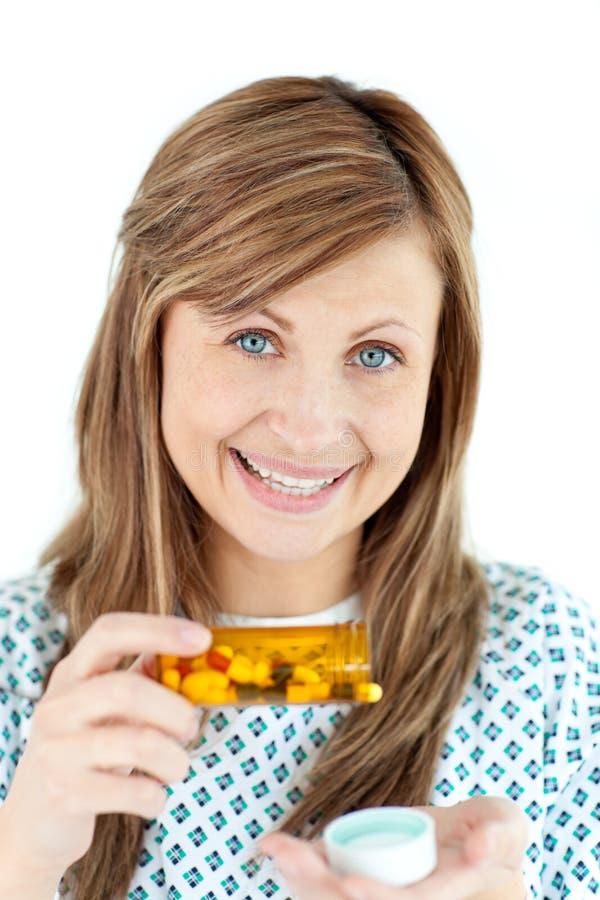 Glimlachende jonge vrouw die pillen neemt royalty-vrije stock fotografie