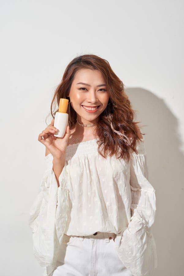Glimlachende jonge vrouw die skincare producten tonen stock fotografie