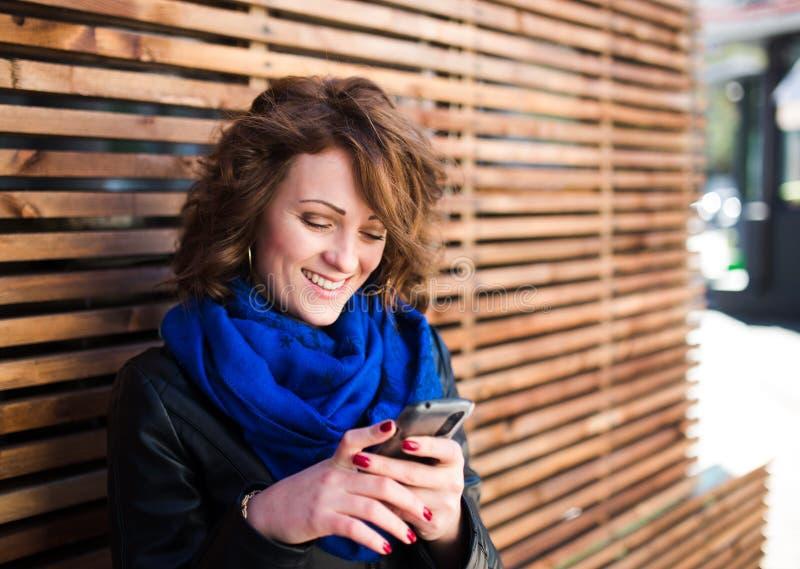 Glimlachende jonge vrouw die smartphone op de straat gebruiken stock fotografie