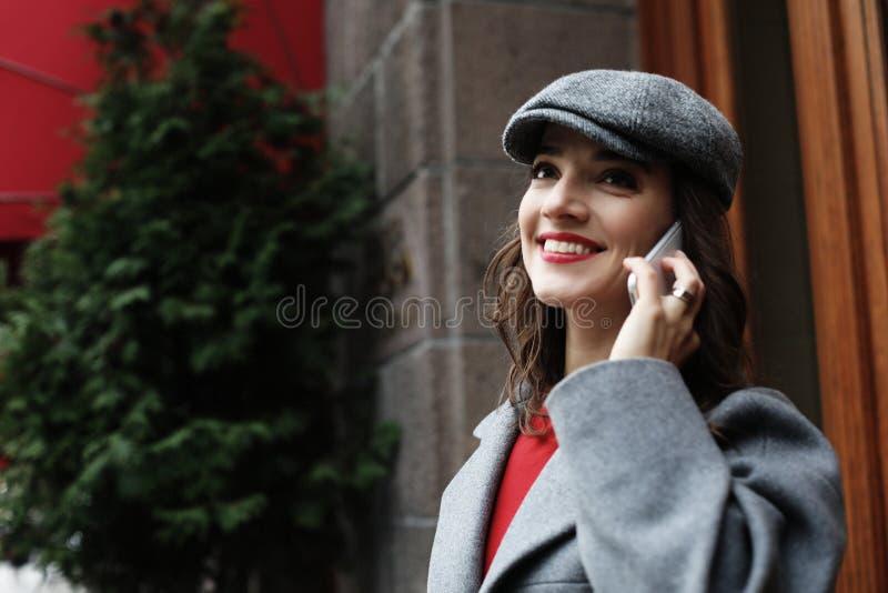 Glimlachende jonge vrouw die smartphone op stadsstraat uitnodigen stock afbeeldingen