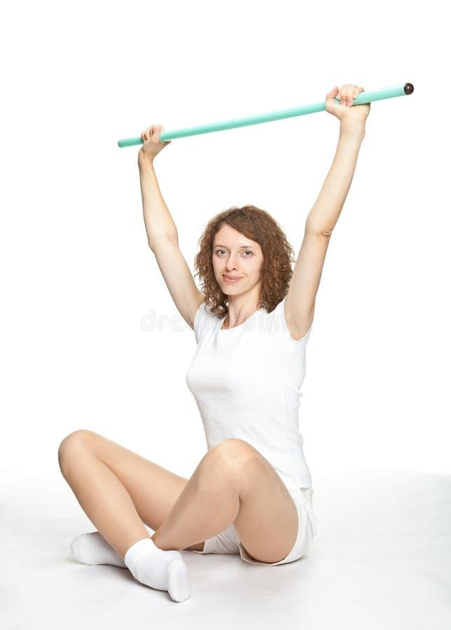 Glimlachende jonge vrouw die sportoefeningen doet stock foto