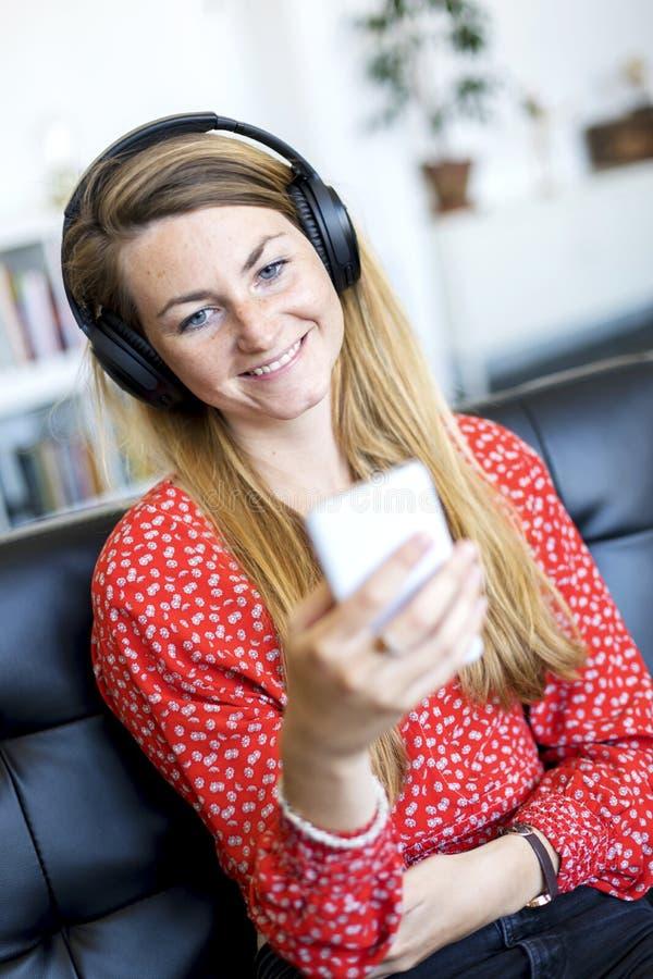 Glimlachende jonge vrouw die thuis op de laag ontspannen stock foto's