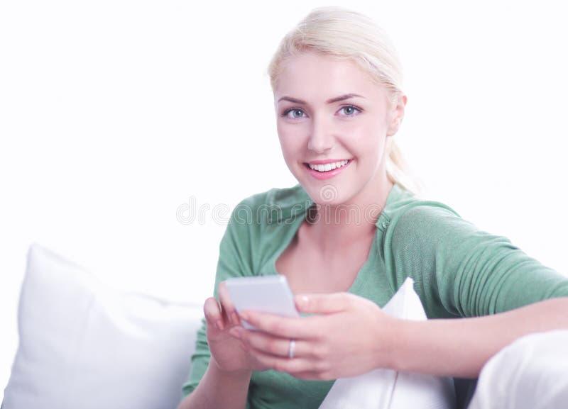 Glimlachende jonge vrouw die thuis op de laag ontspannen, gebruikt zij een smartphone en het texting royalty-vrije stock foto