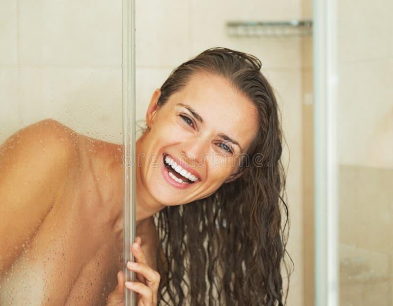Glimlachende jonge vrouw die uit van douchecabine kijkt stock afbeeldingen