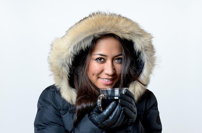 Glimlachende jonge vrouw die van een hete drank genieten royalty-vrije stock afbeelding