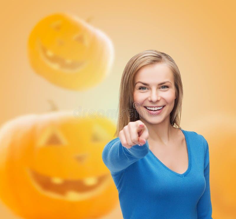 Glimlachende jonge vrouw die vinger richten op u stock fotografie