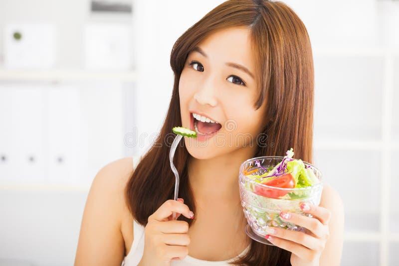 Glimlachende jonge vrouw die vruchten en salade eten stock afbeeldingen